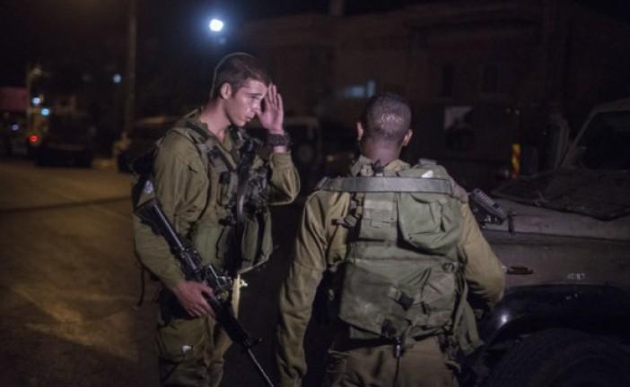 Deux soldats de Tsahal arrêtent un palestinien portant un engin explosif.