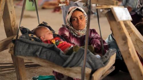 crédits/photos : AFP Une femme irakienne Yazidi, qui a fui son domicile lorsque des militants de l'État islamique ont attaqué la ville de Sinjar, avec son bébé à l'intérieur d'un bâtiment en cours de construction à la périphérie de la ville kurde de Dohouk, le 16 Août 2014