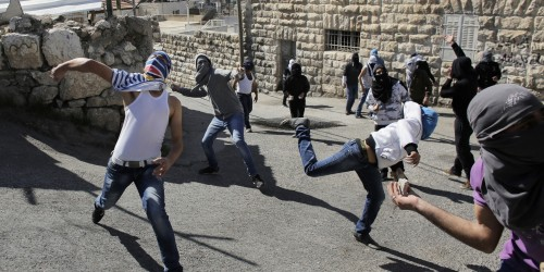 Palestinian protesters throw stones towards Israeli policemen during clashes in the Arab east Jerusalem neighbourhood of Ras al-Amud February 28, 2014. Three Palestinian protesters were detained on Friday during the clashes after they threw stones towards Israeli policemen, a police spokesman said. Israeli security forces were on high alert on Friday ahead of prayers in the Old City of Jerusalem, placing an age limit on Palestinian men wanting to enter the Old City, allowing only males above the age of 50 to enter. The tension comes after an attempt earlier in the week by an Israeli right-wing member of parliament to introduce a bill that calls for the application of Israeli sovereignty over the al-Aqsa mosque compound, located in the Old City. REUTERS/Ammar Awad (JERUSALEM - Tags: POLITICS CIVIL UNREST RELIGION TPX IMAGES OF THE DAY) - RTR3FTPD