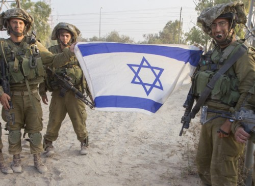 Israeli soldiers pose with a national flag upon their return from combat in the Gaza Strip at an army deployment area near Israel's border with the besieged Palestinian territory on July 23, 2014, as the conflict entered its third week with neither side showing any sign of willingness to pull back. Israel's military pursued a relentless campaign of shelling and air strikes while the Palestinian militants hit back with rocket fire and fierce attacks on troops operating on the ground. Around 650 Palestinians and 29 Israeli soldiers have been killed in the Gaza fighting which began on July 8.  AFP PHOTO / JACK GUEZ