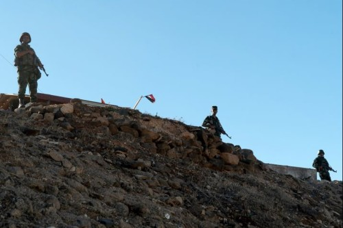 Russian and Syrian soldiers stand guard a hill in Rastan, central Homs province, on August 15, 2018. - Syria's government forces took back the rebel towns of Talbisseh, Rastan, and Al-Houla in May 2018. (Photo by Andrei BORODULIN / AFP)